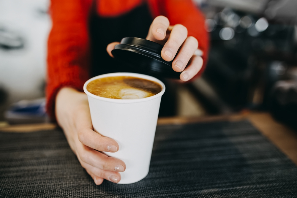 Barista holding hot cappuccino in white takeaway paper cup